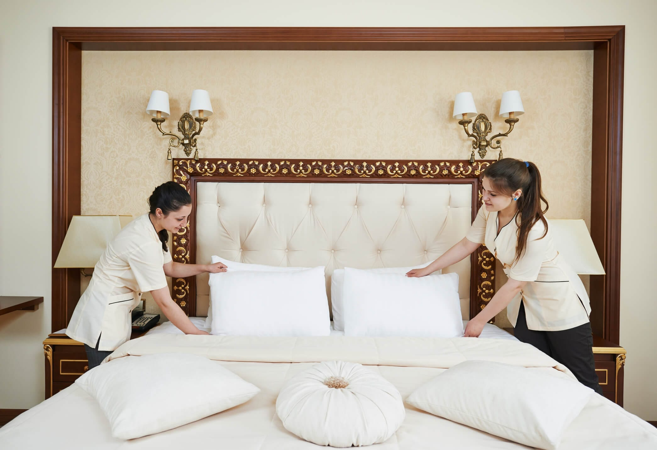 Two Women Making a Hotel Bed with Freshly Cleaned Sheets