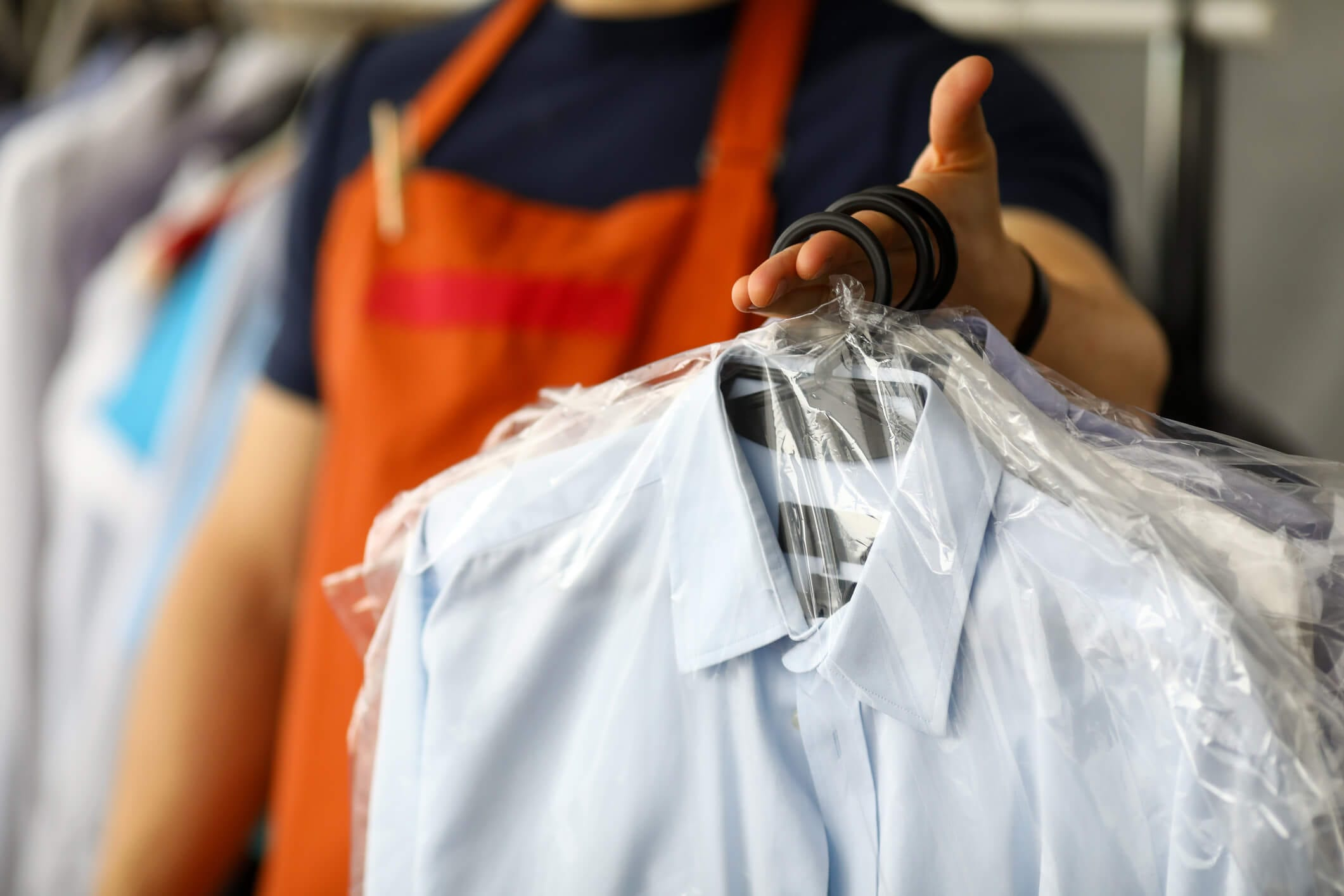 Man Holding Dry Cleaned Shirts on Hangers